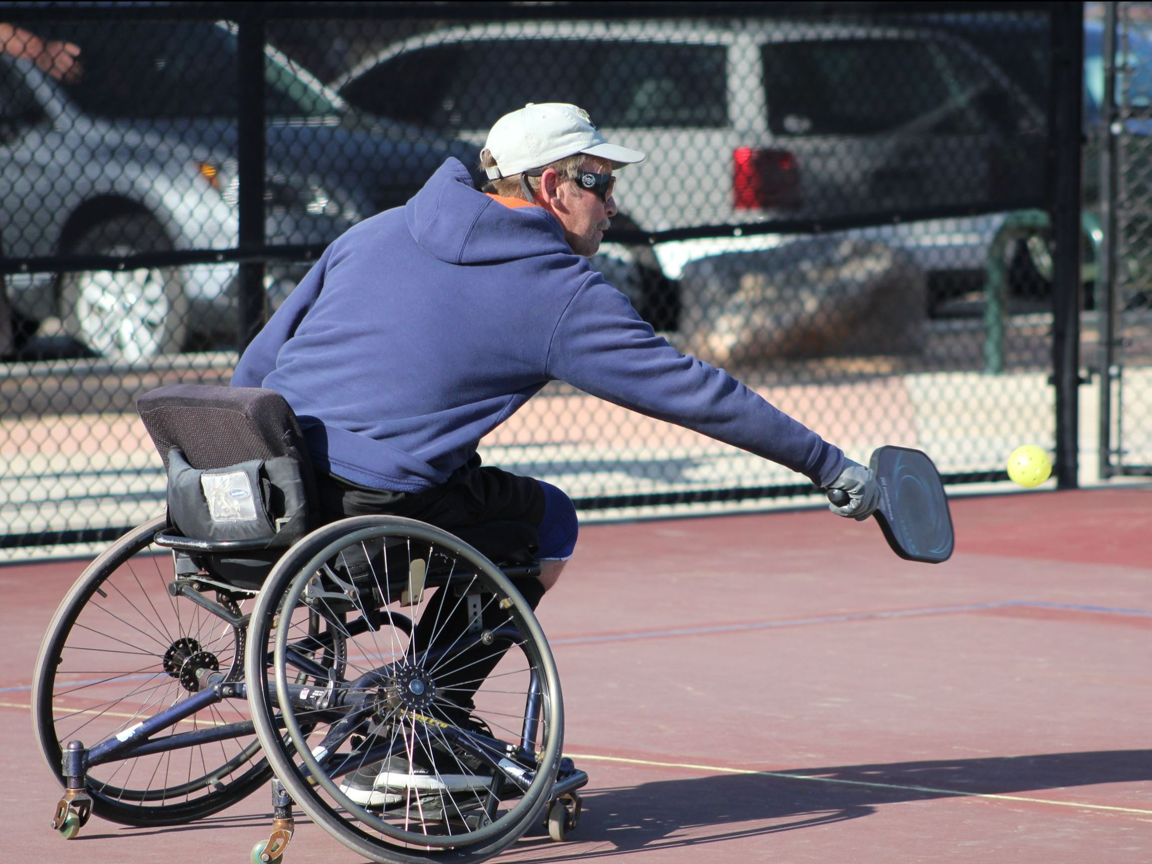 Man in wheelchair playing pickleball